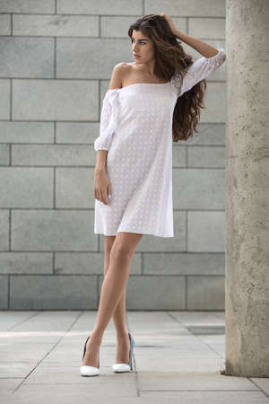 leans on hand: Young girl stands near the concrete column on the background of the wall with tiles. She wears the white dress with dots and the white-blue shoes. Her left elbow leans on the column while hand is on the her head. She looks to the left. Vertical. Stock Photo