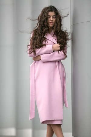 open legs: Cute young girl with streaming hair and crossed legs stands near the columns. She wears pink coat with belt. Her eyes are closed and lips partially open. She clasped her body with hands which holds the coat. Outdoors. Vertical. Stock Photo