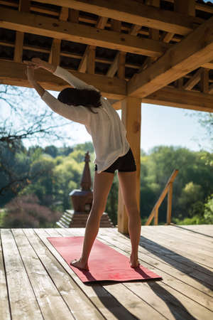 red cardigan: Cute girl is engaged in yoga on the wooden terrace on the nature background. She stands on the red yoga mat and stretches her hands to the left. She wears black shorts and white cardigan. Sunlight falls on her. Photographed from the back. Outdoors. Vertic
