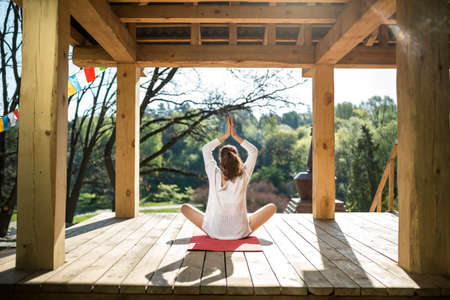red cardigan: Pretty girl is engaged in yoga on the wooden terrace on the nature background. She sits in the lotus pose on the red yoga mat and holds her connected hands over the head. She wears black shorts and white cardigan. Sunlight falls on her. Photographed from