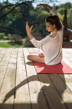red cardigan: Amzing girl is engaged in yoga on the wooden terrace on the nature background. She sits in the lotus pose on the red yoga mat and stretches her hands up. Her head is turned to the left. She wears black shorts and white cardigan. Sunlight falls on her. Pho