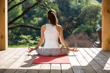Serene girl is meditate in lotus pose on the wooden terrace on the nature background. She sits on the red yoga mat with her hands on the knees. Her index fingers and thumbs are together. She wears white sleeveless t-shirt and gray pants with patterns. Sun Stock Photo