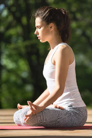 yoga pants: Cute girl with closed eyes is meditate in lotus pose on the wooden terrace on the nature background. She sits on the red yoga mat with her hands on the knees. Her index fingers and thumbs are together. She wears white sleeveless t-shirt and gray pants wit Stock Photo