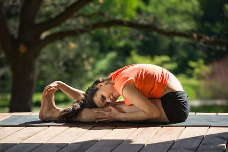 knee bend: Beautiful girl is engaged in yoga on the wooden terrace on the nature background. She seated forward bend on the black yoga mat. Her head lies on the left knee, left hand is on left leg, right hand is on the feet. She looks into the camera. She wears blac