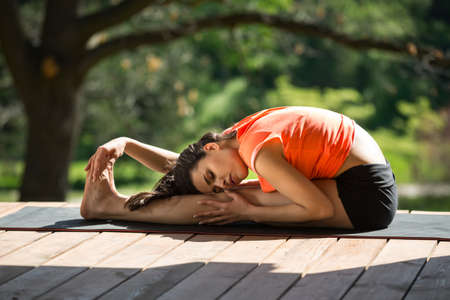 Brunetter girl is engaged in yoga on the wooden terrace on the nature background. She seated forward bend on the black yoga mat. Her head lies on the left knee, left hand is on left leg, right hand is on the feet. Her eyes are closed. She wears black shor Stock Photo