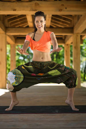 sunligh: Smiling girl does sumo squats on the black yoga mat on the wooden terrace on the nature background. She stands on the toes and holds her hands stretched forward. She looks to the side. She wears orange t-shirt and the wide olive pants with images. Sunligh