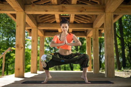 yoga pants: Beautiful girl does sumo squats on the black yoga mat on the wooden terrace on the nature background. She stands on the toes and holds her palms  together. She looks into the camera with a smile. She wears orange t-shirt and the wide olive pants with imag Stock Photo