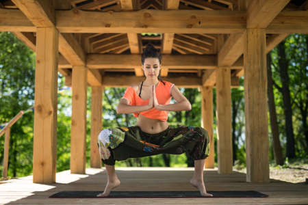 black toes: Cute girl does sumo squats on the black yoga mat on the wooden terrace on the nature background. She stands on the toes and holds her palms  together. She looks at the floor with parted lips. She wears orange t-shirt and the wide olive pants with images.