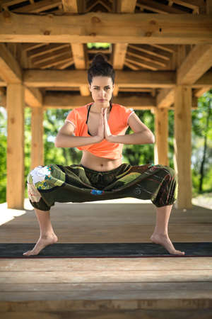 yoga pants: Attractive girl does sumo squats on the black yoga mat on the wooden terrace on the nature background. She stands on the toes and holds her palms  together. She looks into the camera with parted lips. She wears orange t-shirt and the wide olive pants with