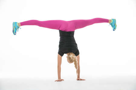 pantalones abajo: Incredible blonde gymnast girl in the sportswear stands upside down on her hands on the white background in the studio. Shoot from the back. She wears cyan-yellow sneakers, pink pants and black t-shirt. She stretches her legs to the sides. She has a plait Foto de archivo