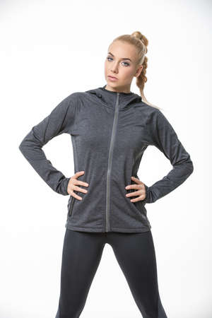 Pretty blonde girl in the sportswear stands on the white background in the studio. She wears black-gray pants and gray hoody. She holds her hands on her waist. She looks into the camera. She has a plait on her head. Vertical.