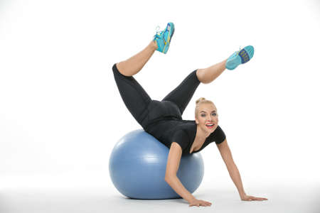 Blonde girl in the sportswear lies on a blue fitball on the white background in the studio. She wears cyan-yellow sneakers, black pants and black t-shirt. She leans on her hands, her torso is on the fitball, her legs are in the air and bended forward. She