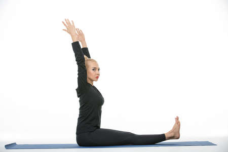 black toes: Beautiful blonde girl in the sportswear does exercise barefoot on the white background in the studio. She wears black pants and black long sleeve t-shirt. She sits on a blue gymnastic mat with arms stretched up. Her toes looks up. She looks to the side. P