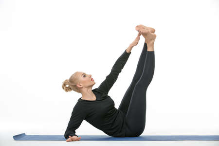 elbow white sleeve: Sportive blonde girl in the sportswear does exercise barefoot on the white background in the studio. She wears black pants and black long sleeve t-shirt. She is on a blue gymnastic mat. She leans on the right elbow, legs are stretched up and the left hand Stock Photo