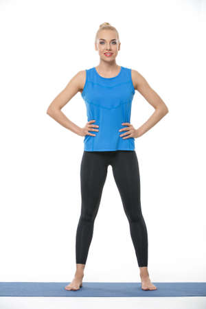 barefoot blonde: Pretty blonde girl in the sportswear stands on a blue gymnastic mat on the white background in the studio. She wears black pants and blue sleeveless t-shirt. She is barefoot. She holds her hands on the waist. She looks into the camera with a smile. Vertic
