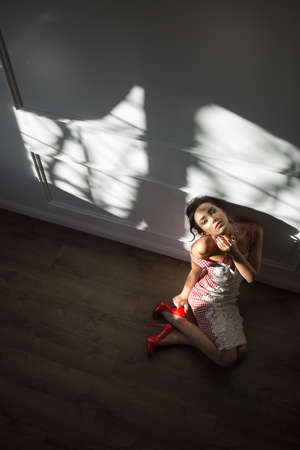leans on hand: Young girl leans on a light wall while sitting on the floor in the interior. She wears a red and white dress with red shoes. She looks into the camera with crossed legs. She holds right hand on right shoe while holding left hand on her neck. Daylight fall Stock Photo