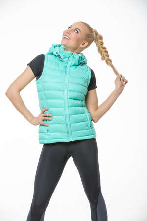 Pretty blonde girl in the sportswear stands on the white background in the studio. She wears black-gray pants, black t-shirt and mint vest. She holds her right hand on her waist. She holds her plait with left hand. She looks to the right and up with a smi Reklamní fotografie