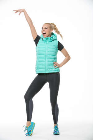 hand lifted: Sportive laughing blonde girl in the sportswear stands on the white background in the studio. She wears cyan-yellow sneakers, black-gray pants, black t-shirt and mint vest. She holds her left hand on her waist, right hand lifted up, right leg is on the to
