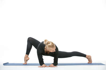 long toes: Cool blonde girl in the sportswear makes the splits on a blue gymnastic mat on the white background in the studio. She wears black pants and black long sleeve t-shirt. She is barefoot. She leans on her elbows and palms, while legs are on the toes. She loo
