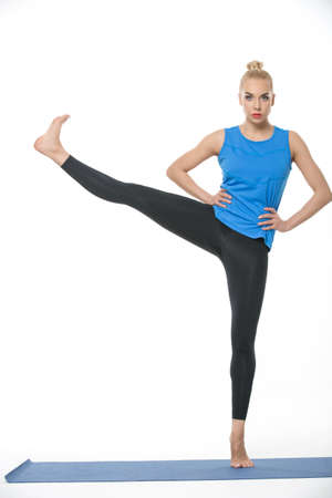 barefoot blonde: Sportive blonde girl in the sportswear stands on the left leg on a blue gymnastic mat on the white background in the studio. She wears black pants and blue sleeveless t-shirt. She is barefoot. She holds her hands on the waist. Her right leg raised and str