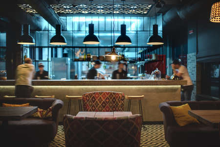 Half-lighted hall in a loft style in a mexican restaurant with open kitchen on the background. In front of the kitchen there are wooden tables with multi-colored chairs and sofas. On the sofas there are color pillows. In the kitchen there is a rack with w