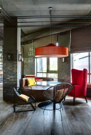 Room in a mexican restaurant in a loft style. There is a glass rounded table with black chairs, a crimson armchair and a brown sofa. Over them there is a red lampshade. Multi-colored pillows lies on the sofa and the chairs. Near the sofa there is a brick