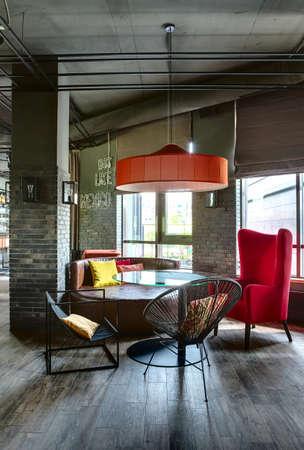 Zimmer in einem mexikanischen Restaurant in einem Loft-Stil. Es ist ein Glas abgerundet Tisch mit schwarzen Stühlen, einem roten Sessel und einem braunen Sofa. Über sie gibt es einen roten Lampenschirm. Mehrfarbige Kissen liegt auf dem Sofa und die Stühle. In der Nähe des Sofa gibt es einen Ziegel Standard-Bild - 57627637