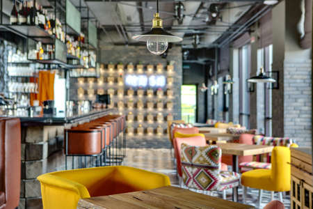 Wonderful bar in a mexican restaurant in a loft style. On the left there is a black bar rack with brown chairs, shelves with dishes and equipment. On the right there are wooden tables with multi-colored chairs, windows with curtains. At the top there are