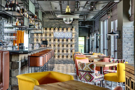 Charming bar in a mexican restaurant in a loft style. On the left there is a black bar rack with brown chairs, shelves with dishes and equipment. On the right there are wooden tables with multi-colored chairs, windows with curtains. At the end there is a