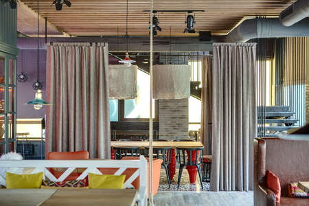 orange chairs: Mexican restaurant in a loft style. On the left there is a wooden table with white sofa with multi-colored pillows, a wooden table with orange chairs, a cupboard with glass doors. On the right there is a brown sofa with color pillows, a black stair. On th