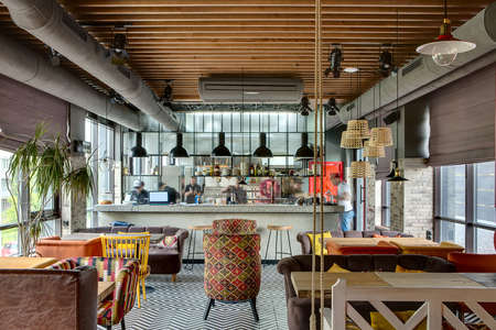 Fantastic interior in a loft style in a mexican restaurant with open kitchen on the background. In front of the kitchen there are wooden tables with multi-colored chairs and sofas. On the sofas there are color pillows. In the kitchen there is a rack with