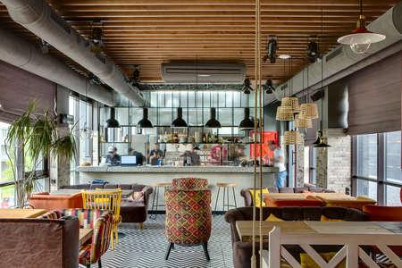 interior fantástico en un estilo loft en un restaurante mexicano con cocina abierta en el fondo. En frente de la cocina hay mesas de madera con sillas y sofás multicolores. En los sofás que hay almohadas de color. En la cocina hay un estante con Foto de archivo