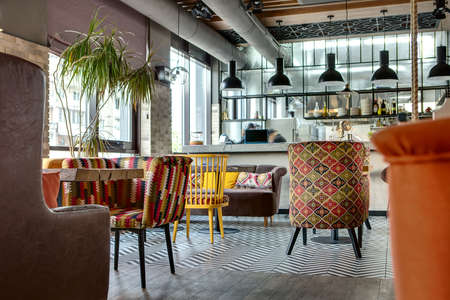 Charming hall in a loft style in a mexican restaurant with open kitchen on the background. In front of the kitchen there are wooden tables with multi-colored chairs and sofas. On the sofas there are color pillows. In the kitchen there is a rack with lapto Zdjęcie Seryjne - 57741407