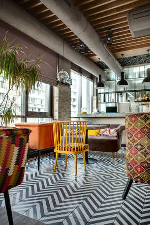 Nice hall in a loft style in a mexican restaurant with open kitchen on the background. In front of the kitchen there are wooden tables with multi-colored chairs and a brown sofa. On the sofa there are color pillows. In the kitchen there is a rack with lap