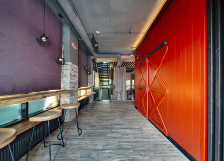 woo: Hall in a loft style in a mexican restaurant. On the left there is a brick wall with curtained windows, wooden racks with wooden chairs near them and black wrought lamps over them. Under the racks there are black radiators. On the right there is a red woo