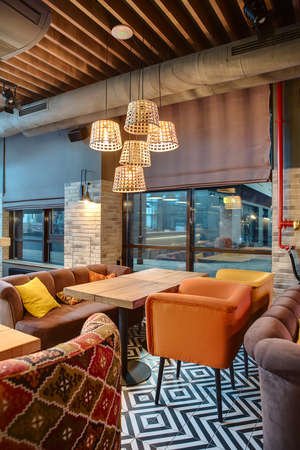 lampshades: Nice room in a mexican restaurant in a loft style. There are several wooden tables with multi-colored chairs and sofas. On the sofas there are color pillows. Over the tables there are glowing wicker lampshades. On the back wall there are windows with curt