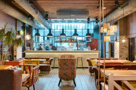 Glowing interior in a loft style in a mexican restaurant with open kitchen on the background. In front of the kitchen there are wooden tables with multi-colored chairs and sofas. On the sofas there are color pillows. In the kitchen there is a rack with wo