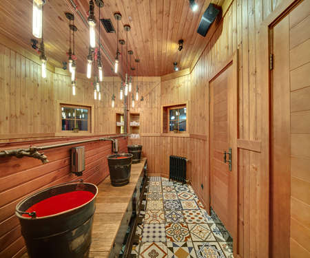 washbasins: Washroom with wooden walls in a mexican restaurant. On the left there are metal-red washbasins in the form of buckets, soap dispensers, metal faucets in the form of a fairy animal, a big mirror. Opposite wall reflected in the mirror. On the back wall ther