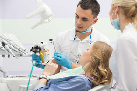 latex girl: Dental cabinet with girl in blue shirt and patient bib on the patient chair. Near her sits a male dentist and a female assistant. They both wear white uniform with blue latex gloves and blue masks. Dentist also has binocular loupes. He holds an articulato Stock Photo