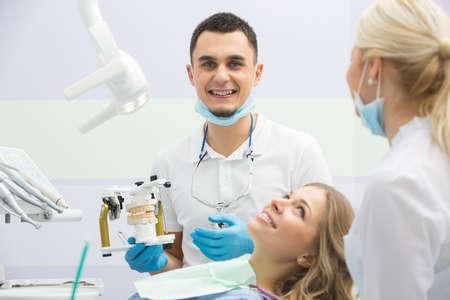 articulator: Happy girl in blue shirt and patient bib in the dental cabinet. Near her there is a smiling male dentist and a female assistant. They both wear white uniform with blue latex gloves and blue masks. Dentist also has binocular loupes. He holds an articulator Stock Photo