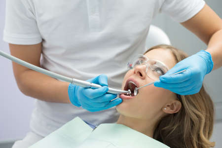 protective eyewear: Brave girl with opened mouth in patient bib and protective eyewear. Next to her there is a dentist in a white uniform with blue latex gloves. He treats her teeth with a LED handpiece and a stem mouth mirror. Horizontal.