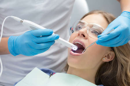 Lovely girl with opened mouth in patient bib and protective eyewear. Next to her there is a dentist in a white uniform with blue latex gloves. He diagnoses her teeth with a LED intraoral camera and a stem mouth mirror. Horizontal. Stock Photo