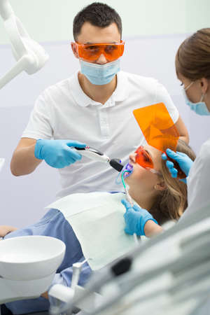 Young girl in blue shirt and patient bib on the patient chair in the dental cabinet. Next to her there is a male dentist and a female assistant. They both wear white uniform with blue latex gloves and blue masks. Patient and dentist wear UV protective eye