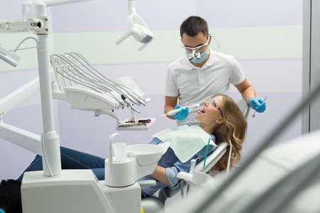 protective eyewear: Dental cabinet with a male dentist and a female patient. He is in the white uniform with blue latex gloves, blue mask, binocular loupes. She is in the blue shirt and jeans on the patient chair. She has a patient bib and a protective eyewear. Dentist holds