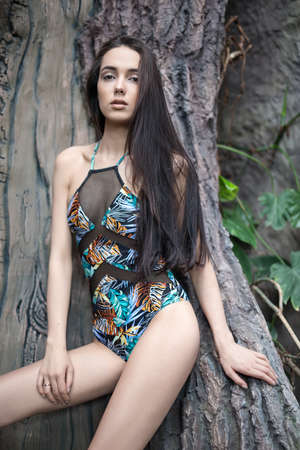 leans on hand: Brunette girl leans on the big tree. She wears a colorful swimsuit with pictures. She holds the right hand on the right leg, left hand is on the tree. She looks into the camera with parted lips. Vertical. Stock Photo