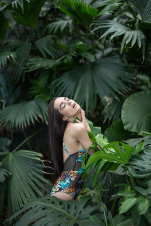 sensuous: Sensuous girl stands sideways between big green plants. She wears a colorful swimsuit with pictures. She presses big leaf to her body with her hands. Her eyes are closed and mouth is open. Vertical.