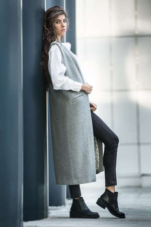 leans on hand: Stylish girl with beautiful hairstyle leans on the column on the wall background. She wears a gray coat without sleeves, a white blouse, dark jeans and black shoes. She holds the coat with right hand and looks into the camera. Her left leg is on the toe,