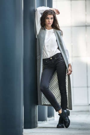 leans on hand: Cute girl with beautiful hairstyle leans on the column on the wall background. She wears a gray coat without sleeves, a white blouse, dark jeans and black shoes. She holds her right hand over the top of her head, left hand hangs along the body. Right leg