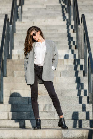 stands: Gorgeous girl with beautiful hairstyle stands on the stair. She wears a gray coat, a white blouse, dark jeans, black shoes and sunglasses. She holds her hands in the pockets. Her head partially turned to the right. Outdoors. Horizontal. Stock Photo