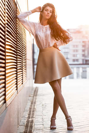 leans on hand: Stylish girl with beautiful hairstyle stands with crossed legs on the blurry urban background. She wears a white blouse, beige skirt and beige sandals. Right elbow leans on the lattice and the right hand leans on the head, left hand is on the waistband. S